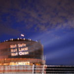 """Text reading """"Not Safe, Not Local, Not Clean"""" projected on the side of large oil tank in the Port of Tacoma"""