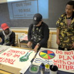 Three people painting protest posters for climate strike.