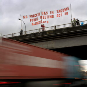 "People stand on highway overpass holding a banner that reads ""no fracked gas in Tacoma, public meeting Oct 30, NoLNG253.org"""