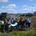 Group of volunteers hold 350 banner at salt marsh