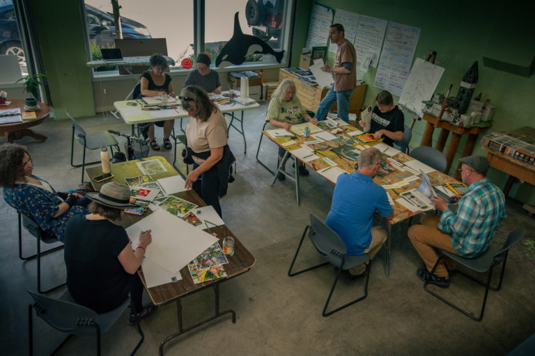 Birds-eye-view of artists gathered around tables constructing collages