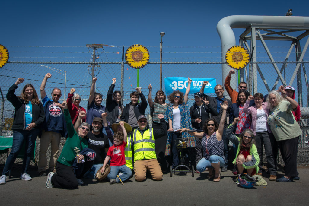 "Group of 20 people smile and raise their fists in front of a chain-link fence with a ""350 Tacoma"" banner hanging"