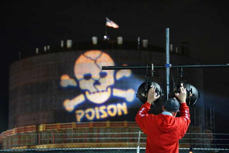 "Person positioning lights that are projecting a skull and cross bones with the word ""poison"" underneath on an oil tank"